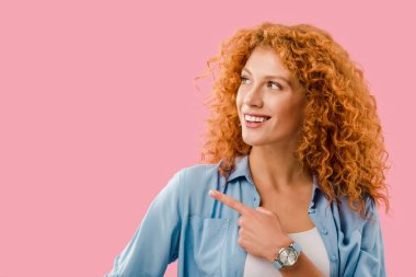 attractive cheerful redhead woman pointing at something isolated on pink