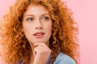 attractive pensive redhead woman isolated on pink