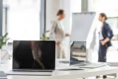 selektivní zaměření dvou obchodních žen, které stojí blízko flipchart a přenosných počítačů na výstupu v kanceláři