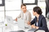 dvě ženy, které sedí u stolu s notebooky a dívají se na sebe