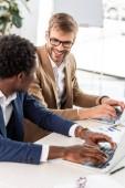 Fotografie dva multietnické podnikatele používající laptopy u stolu v kanceláři