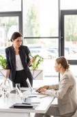 dvě ženy, které se při formálním nošení dívají na sebe a povídají v kanceláři
