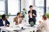 multietnické podnikatele, kteří sedí u stolu během konference v kanceláři