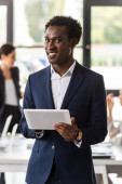Fotografie smiling african american businessman in formal wear holding digital tablet in office