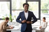 usmívající se africký americký podnikatel ve formálním nošení před kolegy v úřadu