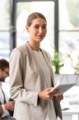 lächelnde schöne Geschäftsfrau mit digitalem Tablet im Büro