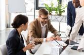 Teilansicht multiethnischer Geschäftsleute am Tisch während der Konferenz im Büro