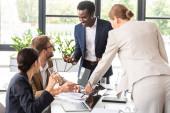 úsměv multietnických podnikatelů při konferenci v kanceláři