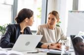 dvě ženy ve formálním opotřebení při konferenci v kanceláři