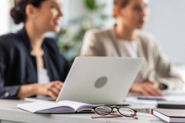 selective focus of two businesswomen and laptop at table in office