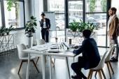 čtyři multietnické kolegy, kteří pracují a používají digitální zařízení v kanceláři