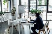 afroamerický podnikatel, který sedí u stolu a používá přenosný počítač