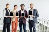 čtyři multietnické kolegy držící digitální tablety a usmívající se v konferenční síni
