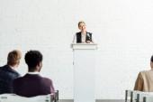 atraktivní obchodnice stojící při konferenci v konferenční síni