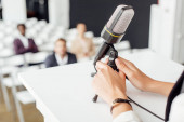 Photo cropped view of businesswoman holding microphone during conference in conference hall