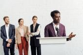 Afrikanisch-amerikanischer Geschäftsmann in offizieller Kleidung spricht während der Konferenz