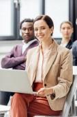 selektiver Fokus attraktiver Frauen in formeller Kleidung mit Laptop während der Konferenz