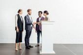 vier multiethnische Kollegen in formellen Tragen sprechen und Hände schütteln im Konferenzsaal