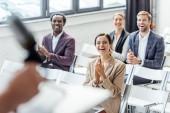 čtyři multietničtí kolegové při konferenci tleskali