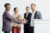 quattro colleghi multietnici in formale usura parlare e stringere la mano nella sala conferenze