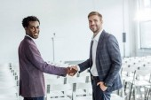Photo two multiethnic colleagues in formal wear shaking hands in conference hall