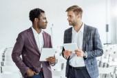 Fotografie dva multietnické kolegy ve formálním oblečení s použitím digitálních tablet v konferenční síni