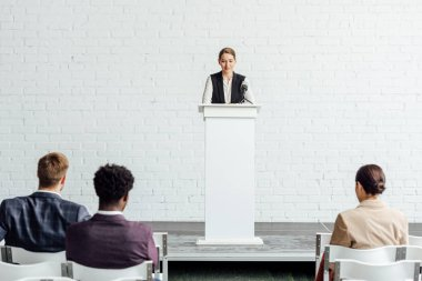 attractive businesswoman standing and talking during conference in conference hall
