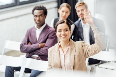 selective focus of attractive woman in formal wear raising hand during conference