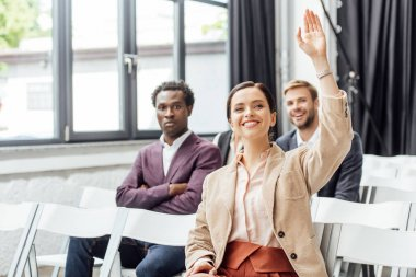 selective focus of attractive businesswoman raising hand during conference
