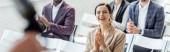 panoramatický záběr atraktivní obchodní ženy usmívající se a tleskání během konference