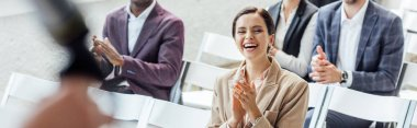 panoramic shot of attractive businesswoman smiling and clapping during conference