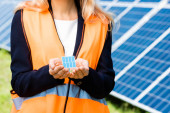 abgeschnittene Ansicht der Geschäftsfrau in Sicherheitsweste mit Solarbatterie-Modell