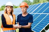 pohledný inženýr a pracovník držící solární model baterie