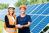 pohledný inženýr a obchodník se usmívající a držící solární model energie