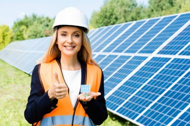 Panoramic shot of businesswoman in safety vest holding solar battery model stock vector