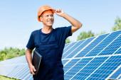 schöner Ingenieur in T-Shirt und orangefarbenem Hut, lächelnd und mit Ordner in der Hand