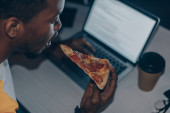 giovane programmatore americano africano mangiare pizza mentre si lavora di notte in ufficio