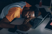 tired african american programmer sleeping on keyboard in office