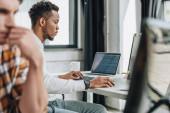 mladý Afričan americký programátor pracující na počítači v blízkosti kolegů