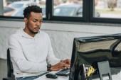Fotografia bello programmatore africano americano che lavora al computer in ufficio