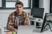 vážný mladý programátor, který se dívá na kameru, když sedí na pracovišti a drží telefon Smartphone