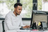 koncentrovaný africký americký programátor pracující na počítači v kanceláři
