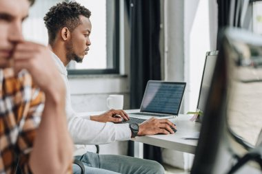 young african american programmer working on computer near colleague