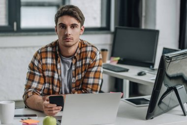 serious young programmer looking at camera while sitting at workplace and holding smartphone