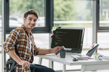 cheerful programmer smiling at camera while sitting near computer monitor with script on screen