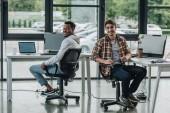 mladí multikulturní programátoři se na kameru usmívají při sezení v kancelářské židli