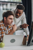 serious african american programmer pointing at computer monitor near thoughtful colleague