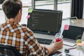 pohled na mladého programátora se sklenicí šťávy při práci na počítači v kanceláři