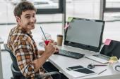 mladý programátor smějící se na kameře a přidržením skleničky šťávy při sezení na pracovišti