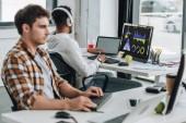 pohled na afroamerického programátora ve sluchátkách sedícího v blízkosti počítačového monitoru s grafy a grafy na obrazovce poblíž kolegy v kanceláři